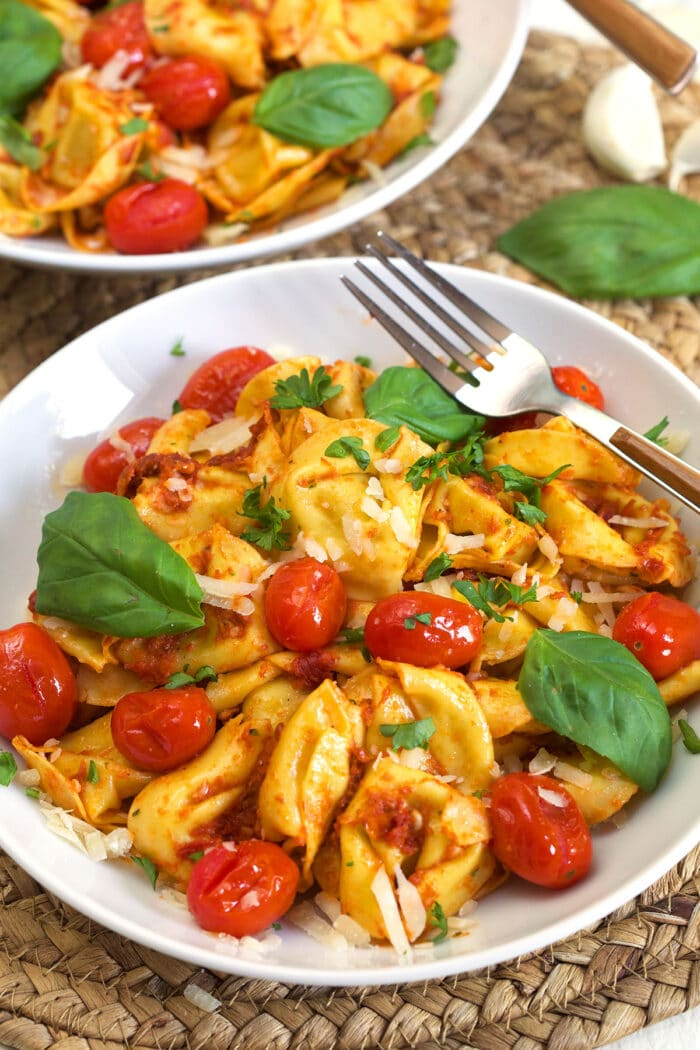 A tortellini bowl is topped with basil, tomatoes, parmesan and parsley.