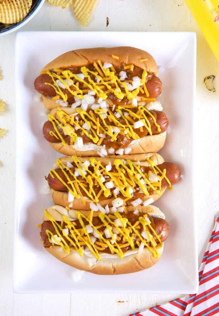 Four hot dogs are placed on a white rectangular plate.