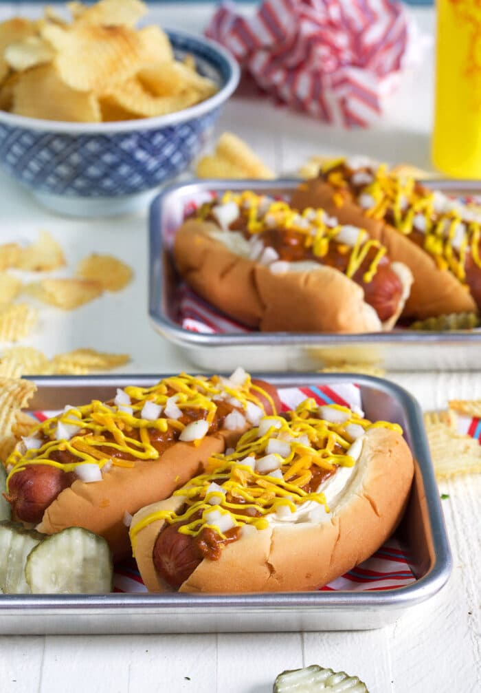 Four hot dogs are placed on two separate metal serving trays.