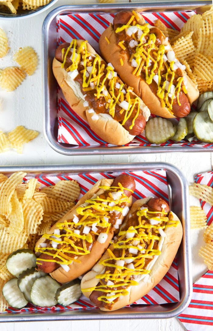 Four hot dogs are ready to be eaten on metal trays.