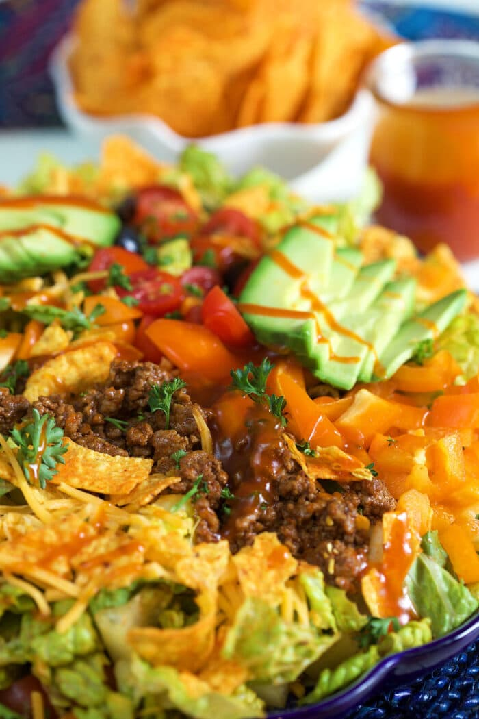 A taco salad is drizzled with dressing.