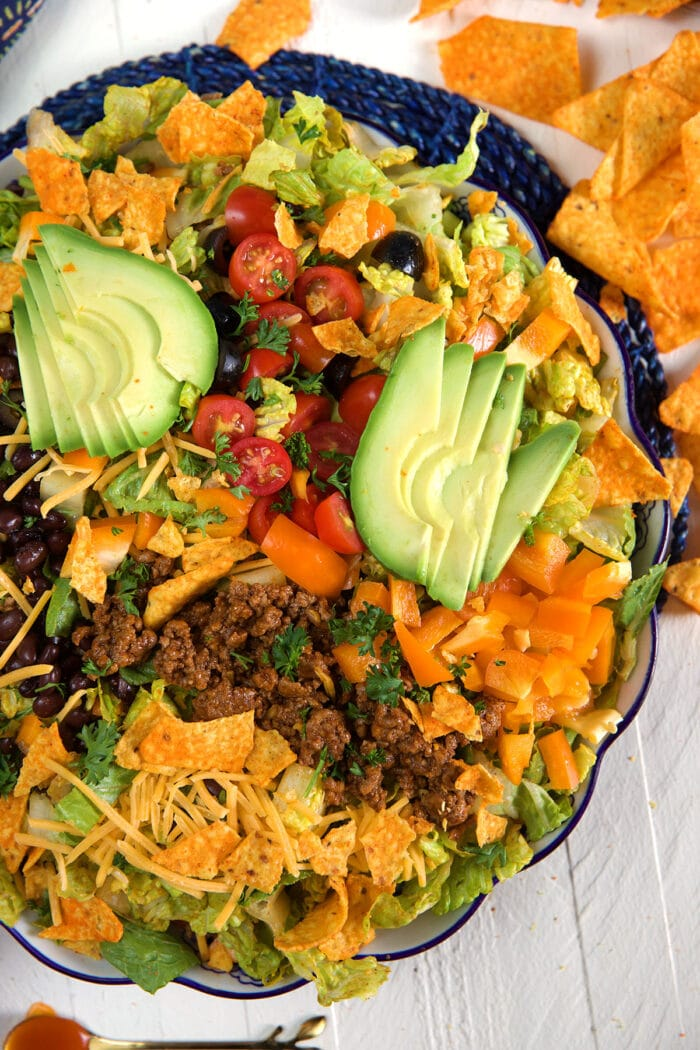 Doritos are spread out on a white surface surrounding a big bowl of taco salad.