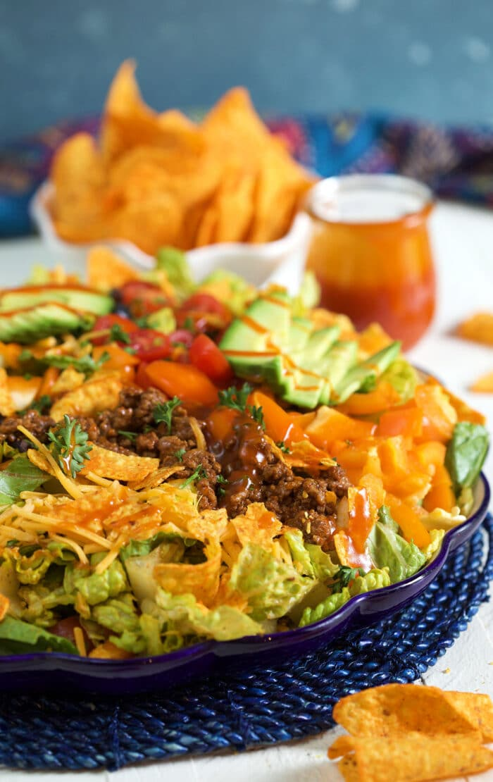 Taco salad is served on a large blue plate and is ready to eat.