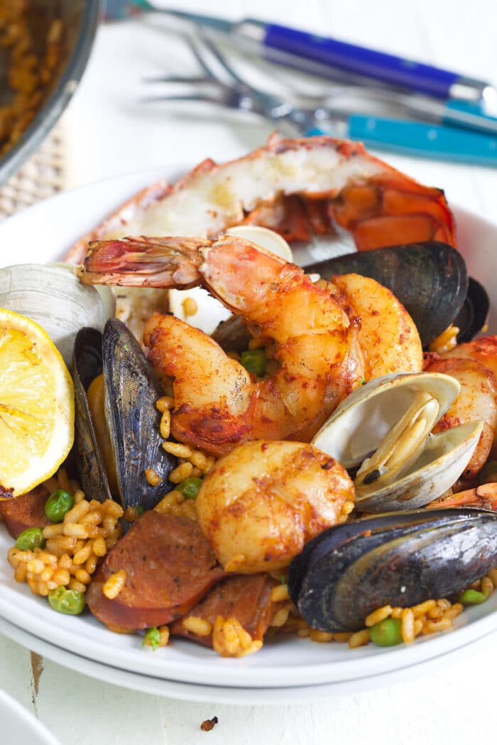 bowl of seafood paella on a white background.