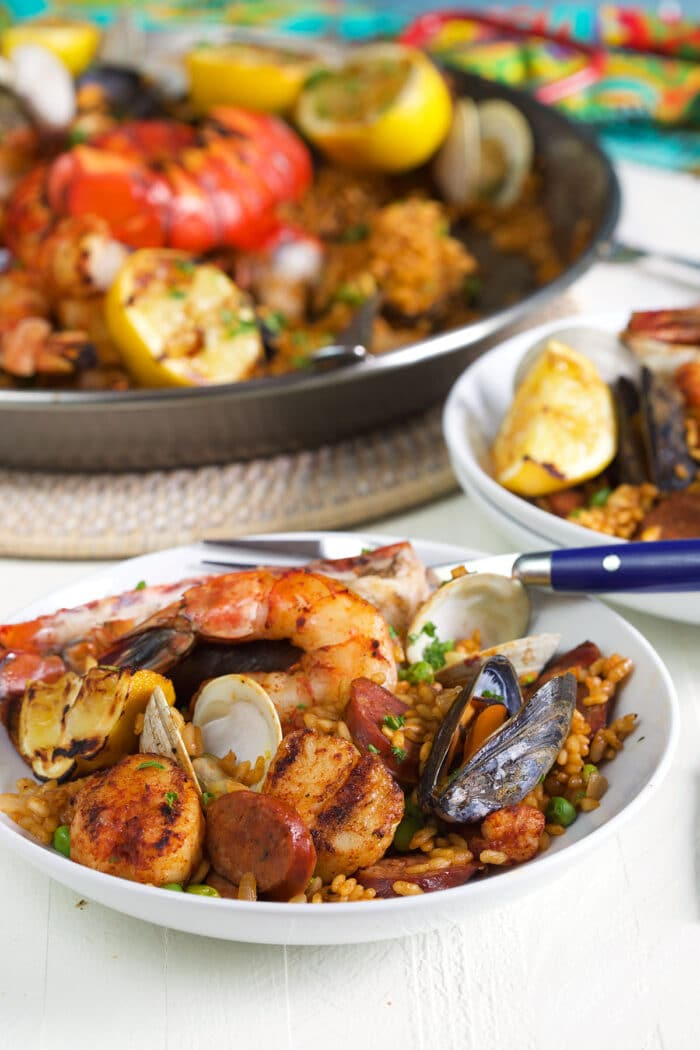 Bowl of seafood paella with a paella pan in the background.