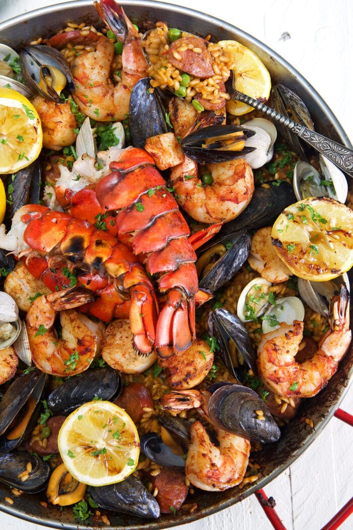 Seafood Paella in a paella pan on a white background.