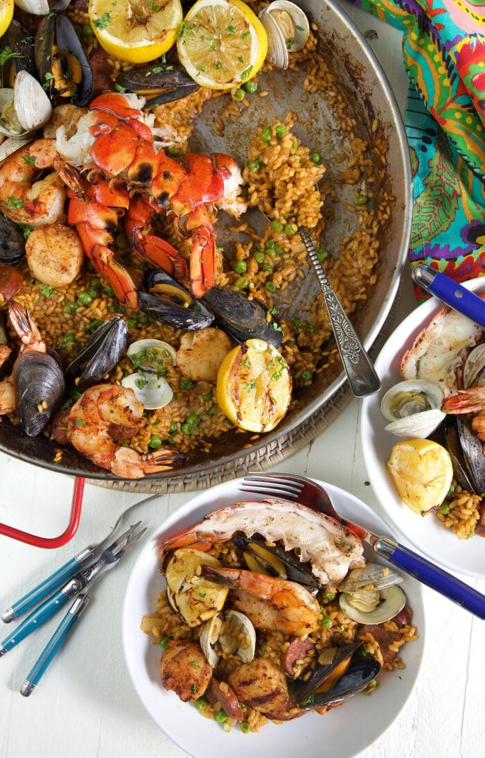 Grilled seafood paella in a paella pan with a bowl of seafood paella on a white background.