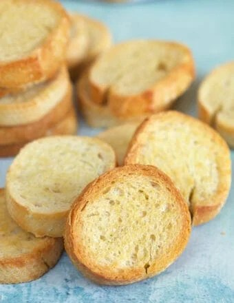 Little golden pieces of crostini are placed on a blue surface.