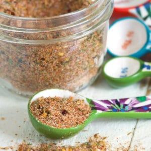 Seasoning has been sprinkled on a white surface next to a teaspoon and jar.