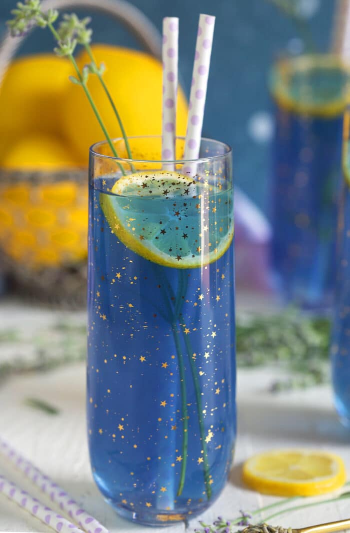 A glass filled with lavender lemonade is on a white surface.