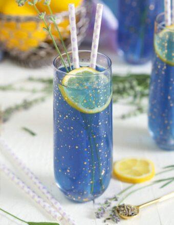 A slice of lemon is in a glass of lavender lemonade.