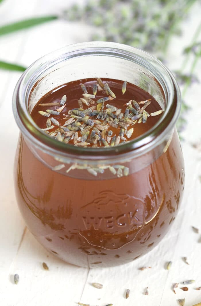 A jar of syrup is garnished with culinary lavender.