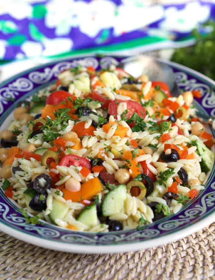 A helping of orzo salad is presented in a blue and white bowl.