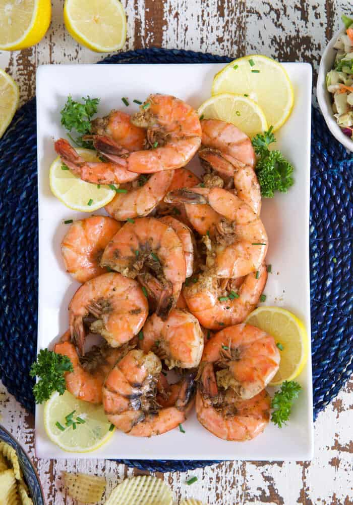 A white plate of steamed shrimp is presented with lemon slices and herbs.