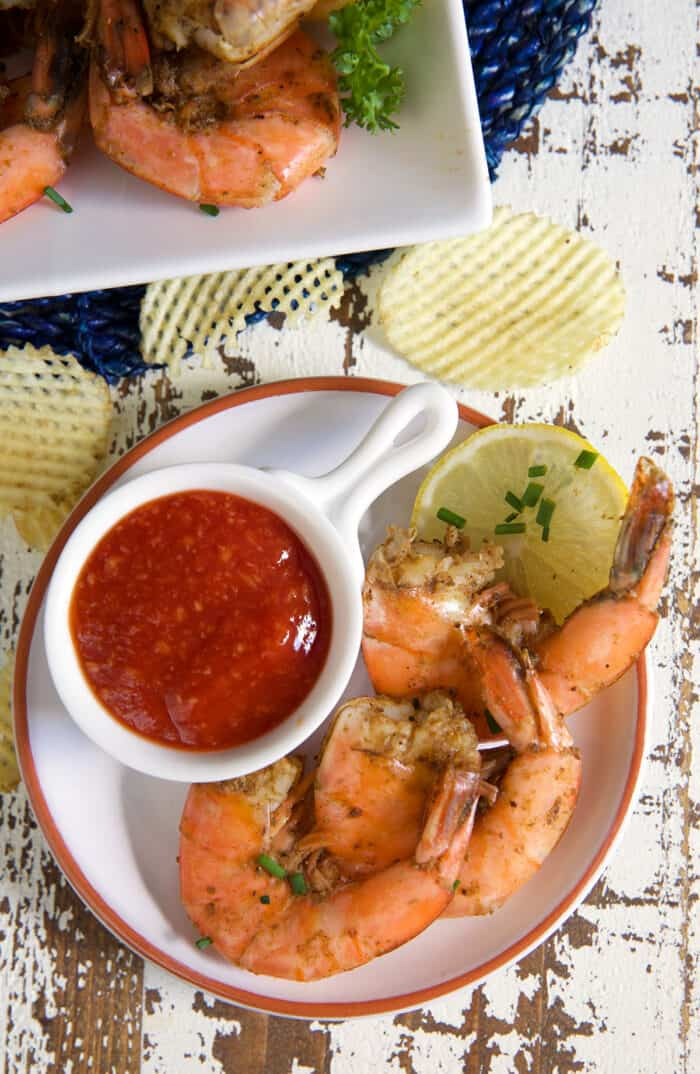 A cup of cocktail sauce is placed next to a serving of shrimp.