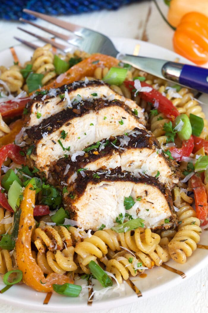 Chicken is sliced and placed on top of pasta.