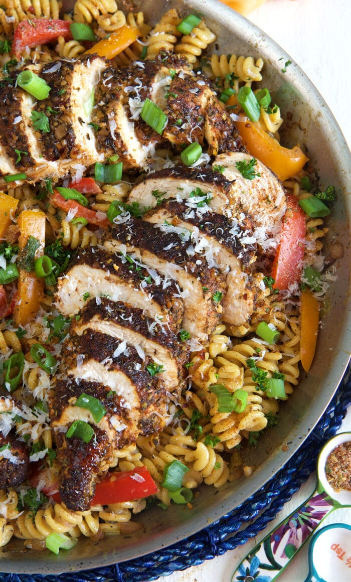 Noodles and chicken are garnished with shredded parmesan cheese.