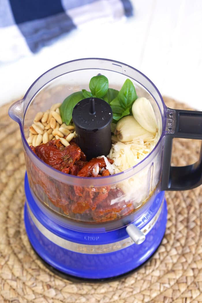 The ingredients for pesto are placed in a food processor.