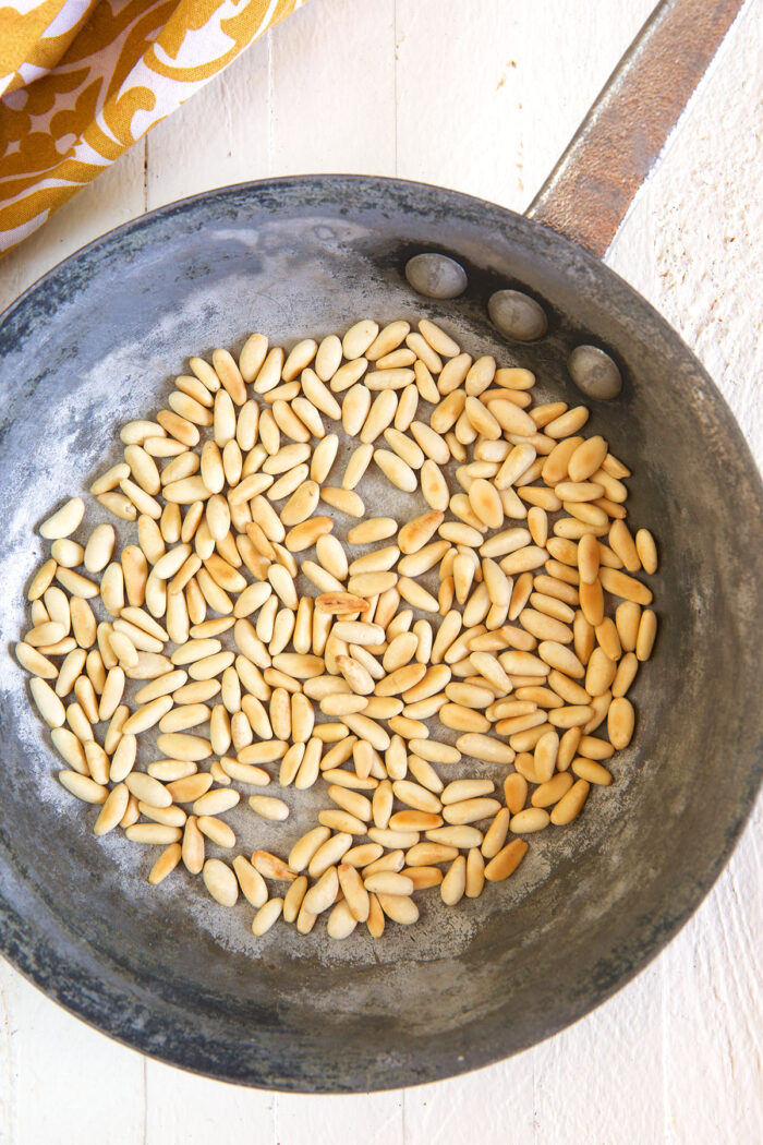 Pine nuts are being toasted in a pan.