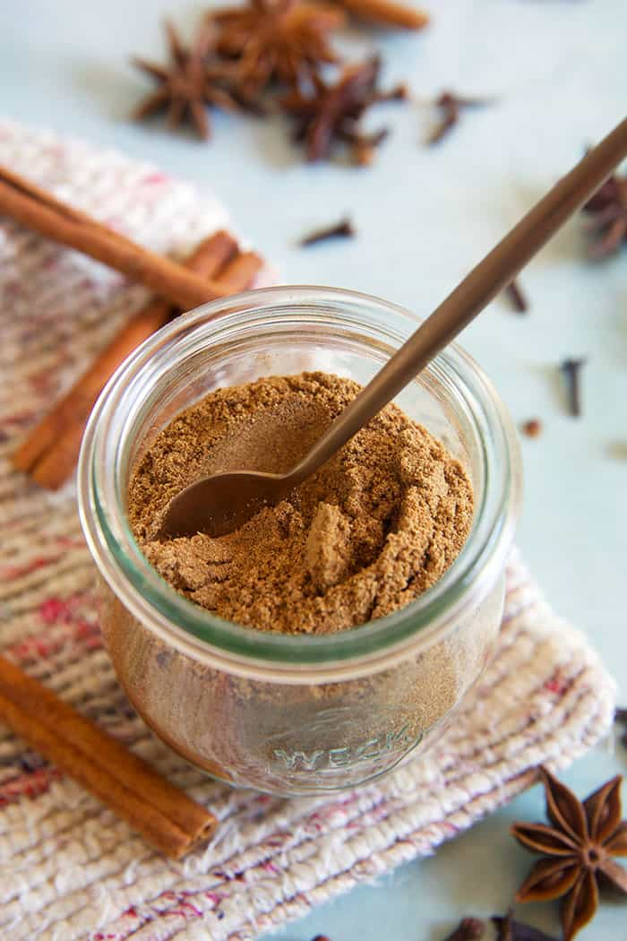 A small spoon is place in a jar of chai spice.
