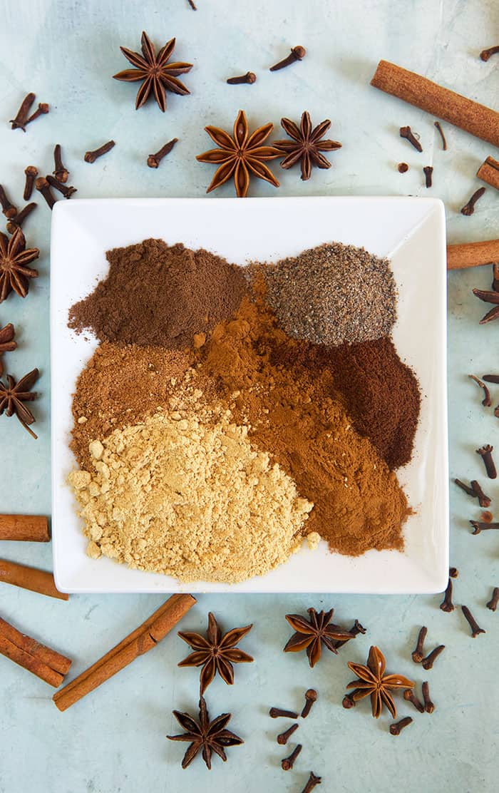 Several spices are on a white square plate, not mixed together.