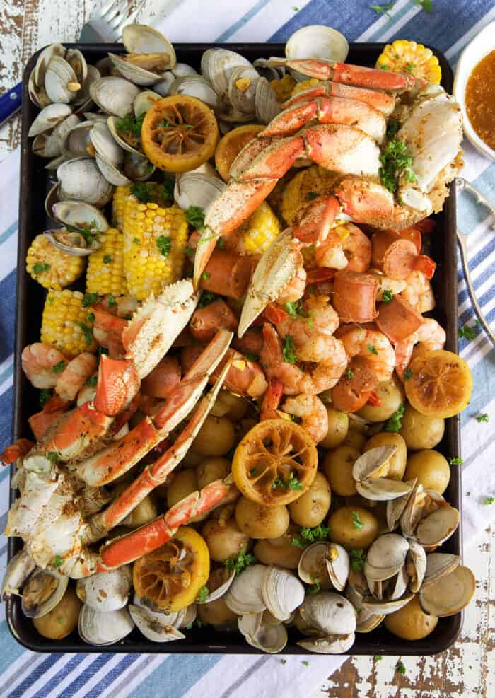 Crab legs, shrimp, clams, corn and potatoes are all boiled and placed on a serving platter.