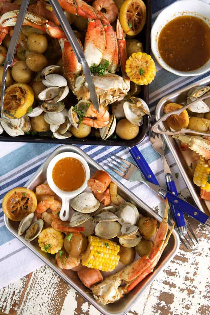 A small rectangular plate is presented with a portion of the seafood boil next to a larger, fuller platter.