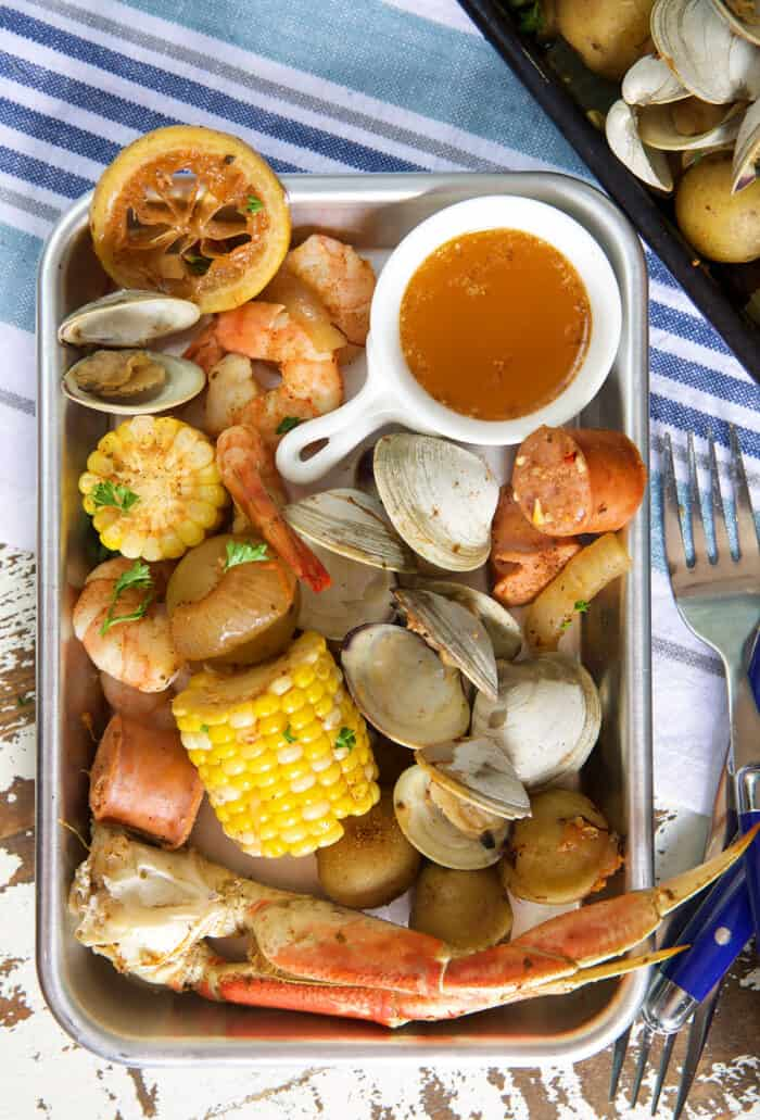 A metal plate is filled with a cajun seafood boil.