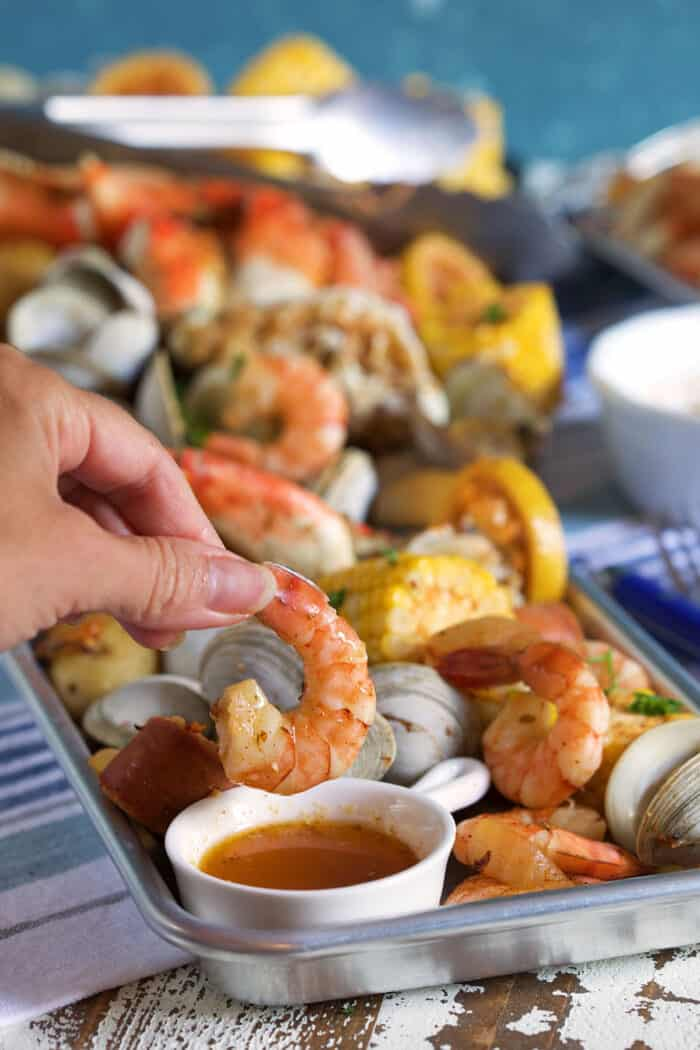 A shrimp is being dipped into a small portion of sauce.