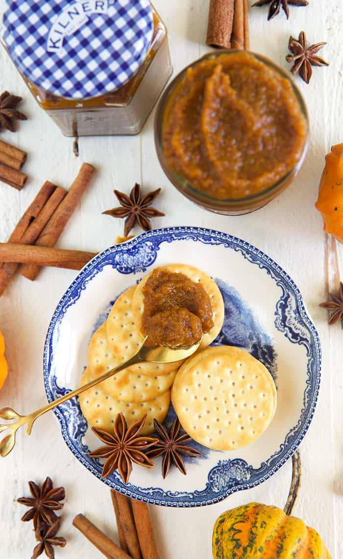 A jar of pumpkin chai butter is placed next to a plate with crackers.