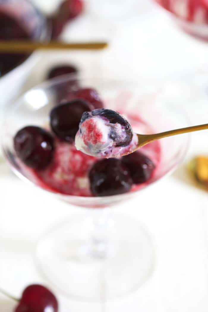 A cherry with ice cream is being lifted from a small glass.