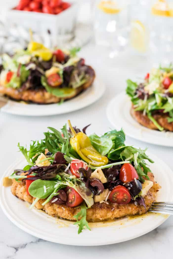 Chicken Milanese with artichoke, tomato salad on top on a white plate.