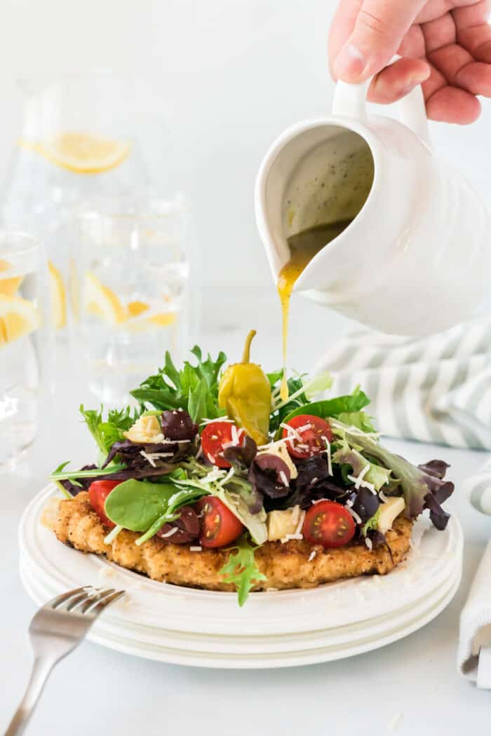 dressing being poured over Chicken Milanese on a white plate.