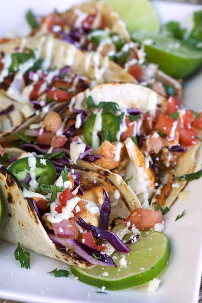 Several fish tacos are presented on a white plate and are all drizzled with avocado ranch dressing.