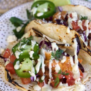 Jalapeno slices and lime wedges are placed on a plate with fish tacos.