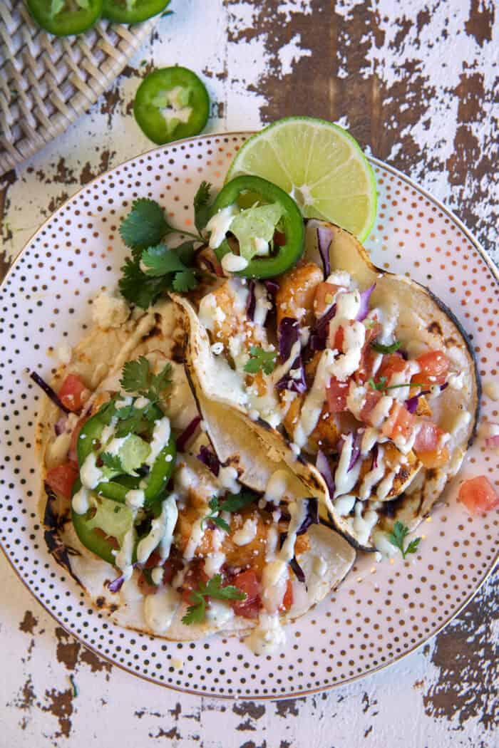 Several cod tacos are on a spotted plate.