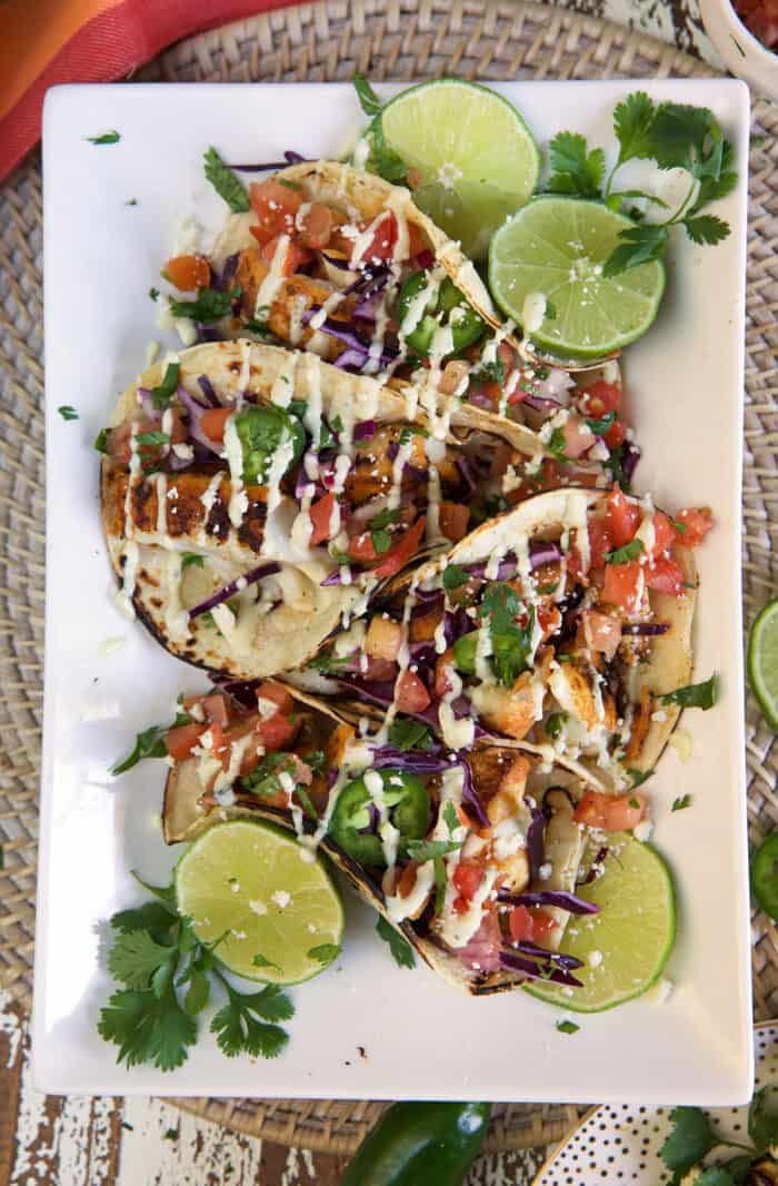Four fish tacos are placed on a rectangular white plate.
