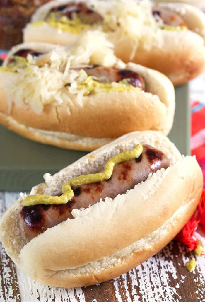 Mustard is drizzled on a beer brat.