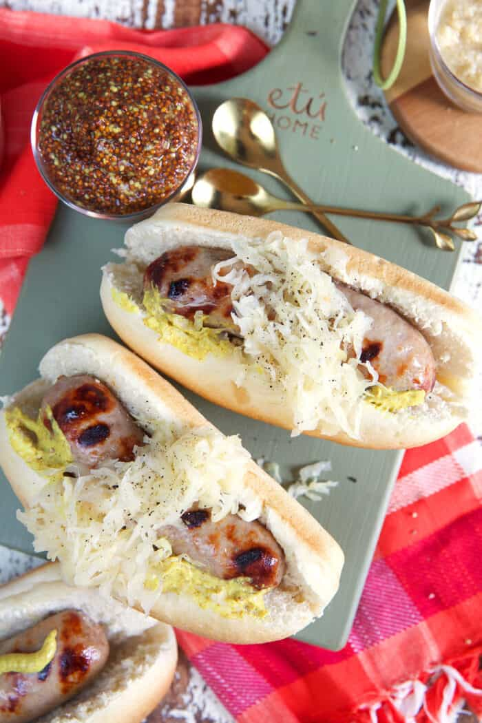 Three beer brats are placed on a green wooden cutting board.