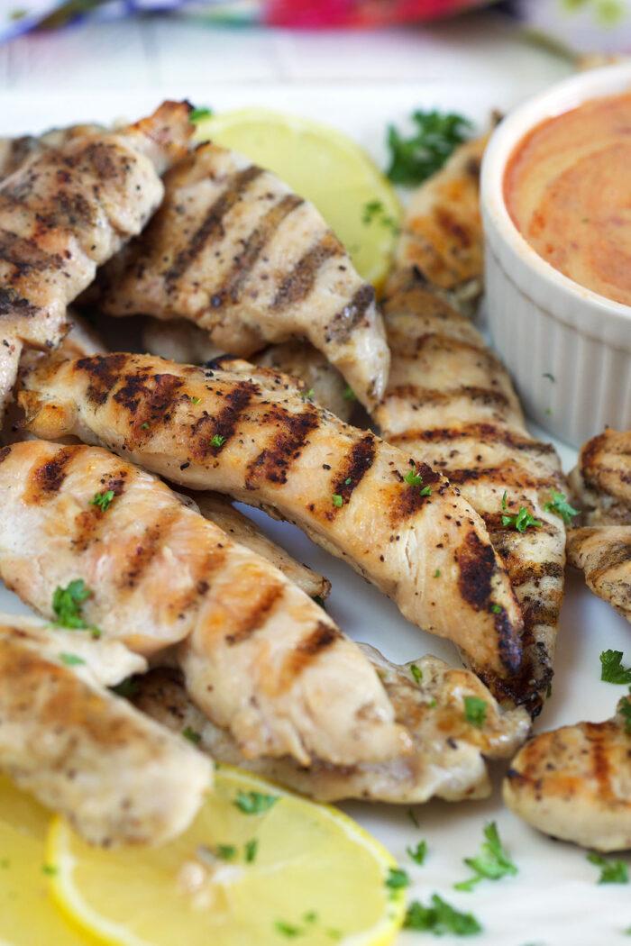Lemon slices garnish a plate of chicken tenders.