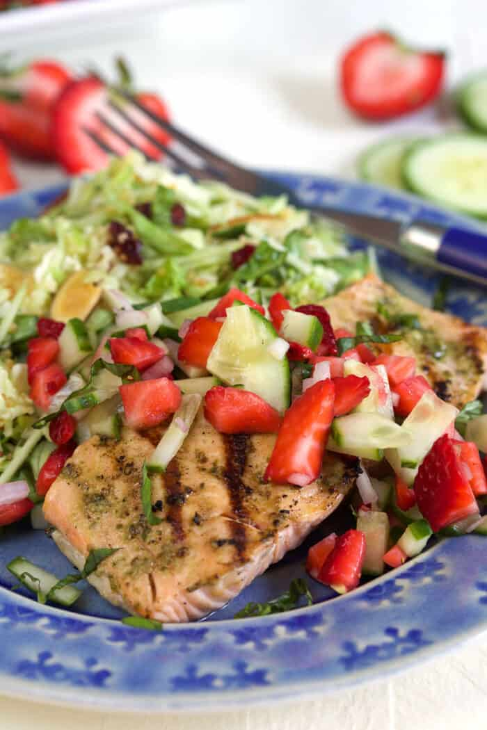 A blue plate is filled with a portion of strawberry salsa and salmon.