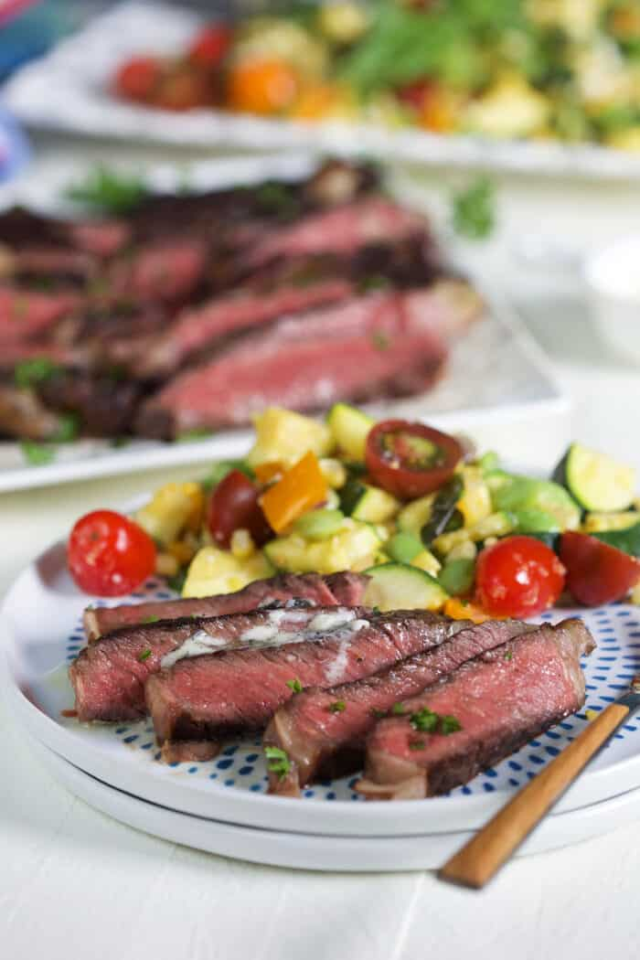 A sliced serving of steak is presented on a blue and white plate.