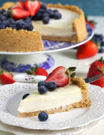 slice of cheesecake on a white plate with a whole cheesecake in the background