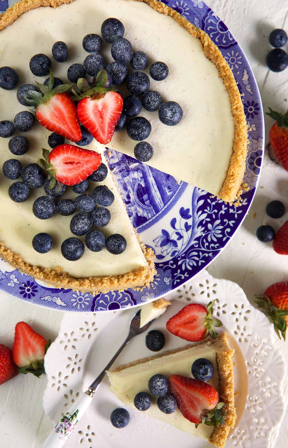 No Bake Cheesecake with blueberries and strawberries on top served on a blue and white cake plate.