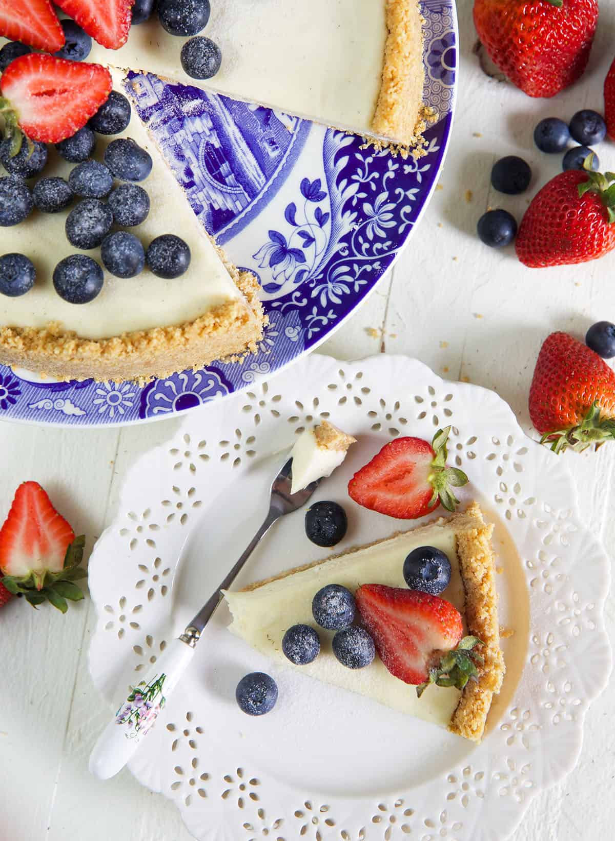 Slice of cheesecake on a white plate with a gold fork and berries on top.