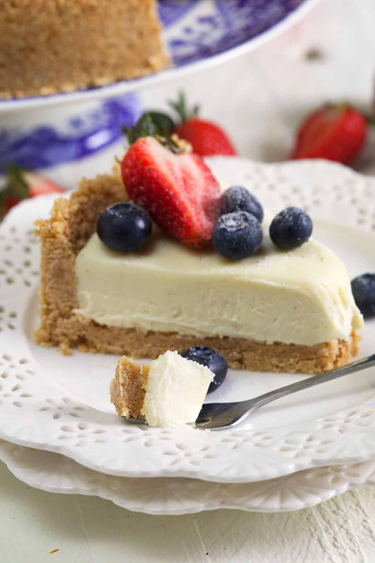 slice of cheesecake on a white plate with a bite on a fork