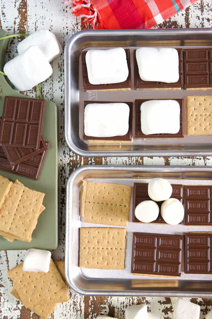 Several graham crackers are topped with marshmallows or various sizes and chocolate.