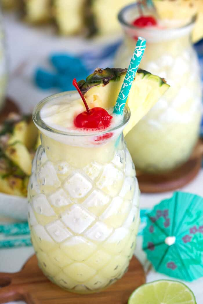 Two pina colada glasses are placed next to each other.