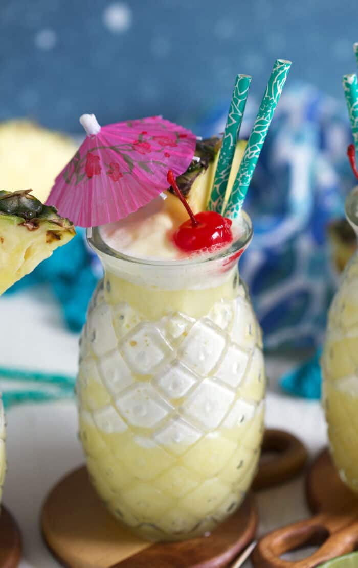 A glass of pina colada cocktail is garnished with an umbrella, pineapple and cherry.