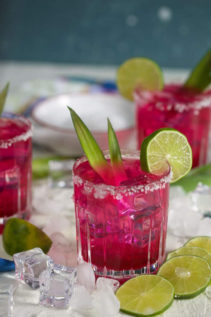 Ice cubes and lime slices are placed around a glass of pink margarita.
